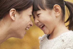 Lachende moeder en dochter met voorhoofden tegen elkaar