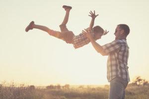 Jongen laat zich vol vertrouwen in de lucht gooien door vader